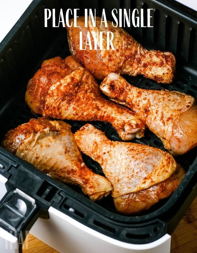 seasoned chicken legs placed in air fryer with text overlay