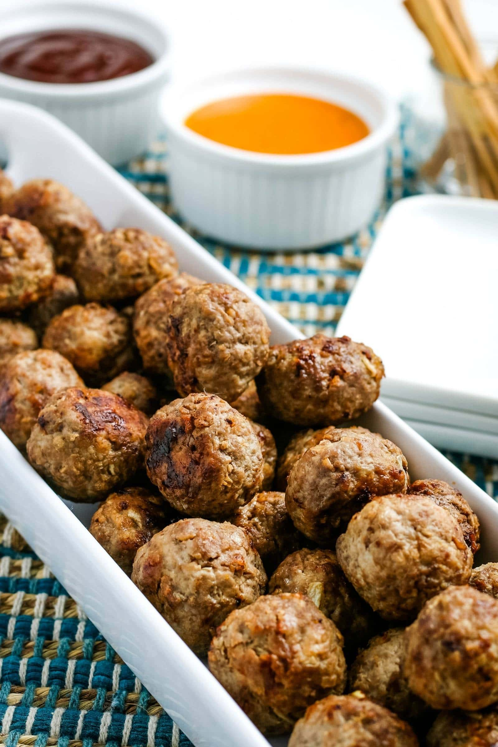 cooked air fryer meatballs on a white plate with dipping sauces in the background