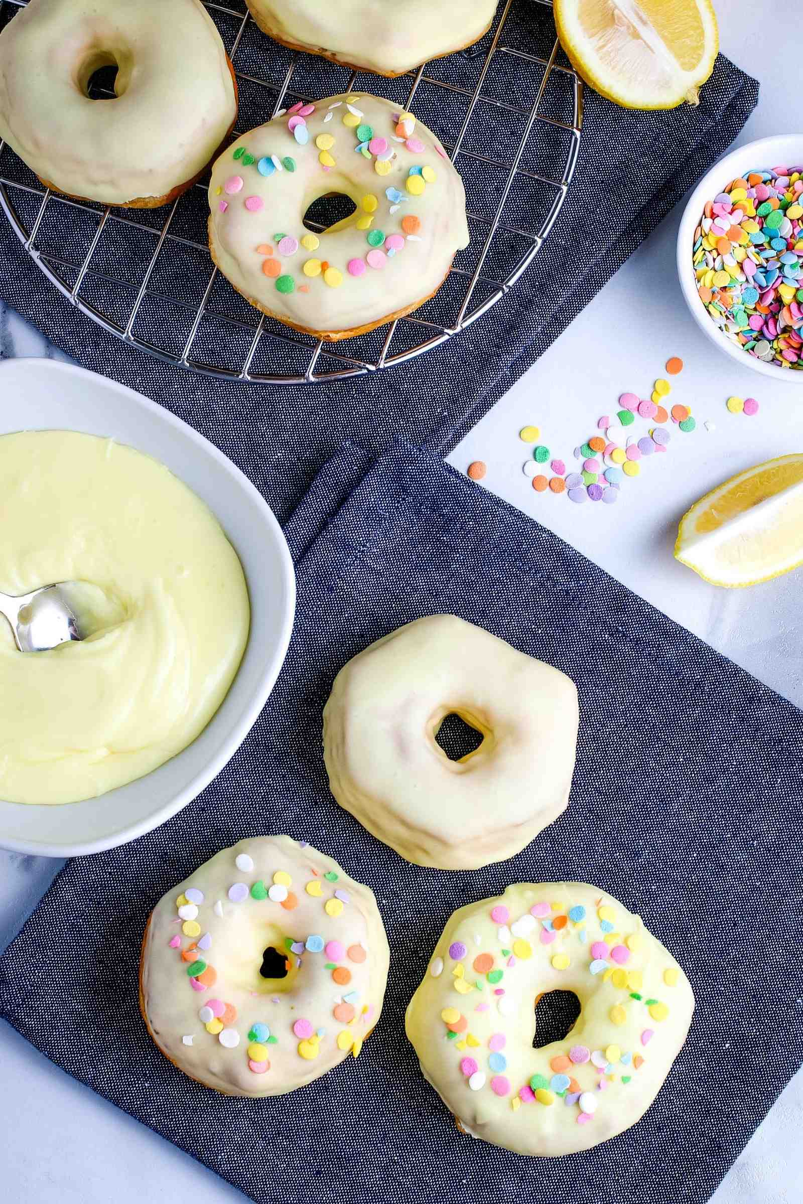 frosted donuts with sprinkles on a black napkin with bowls of frosting and sprinkles