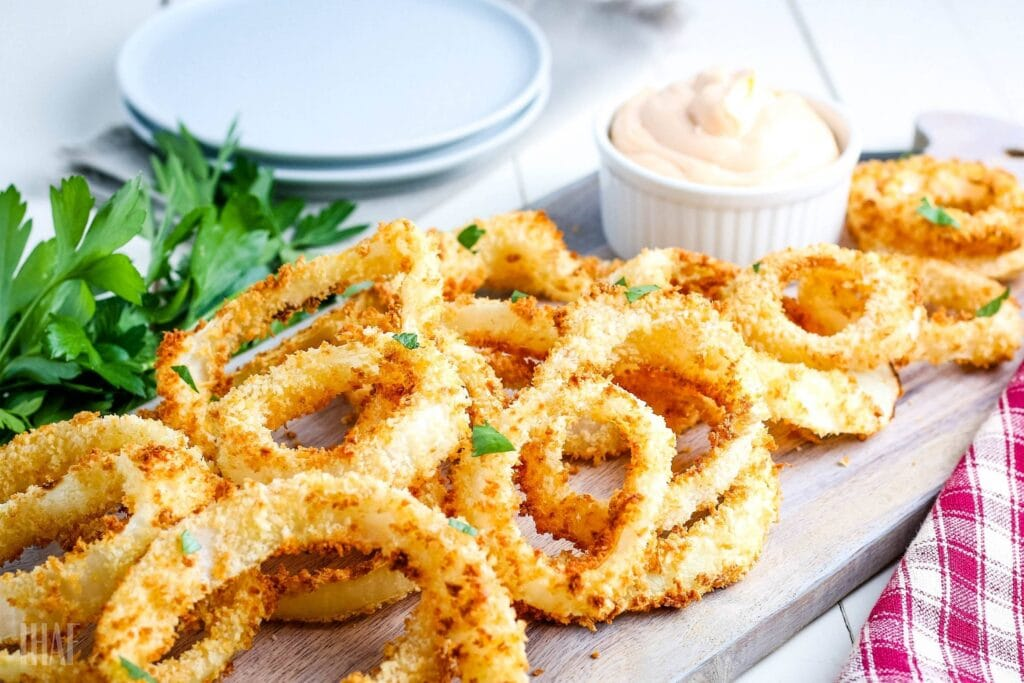 homemade air fried onion rings on a cutting board with sauce and garnish