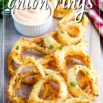 close up of air fried onion rings on a board with a ramekin of sauce and text overlay
