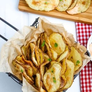 top view of air fried potato chips in a basket and on a board
