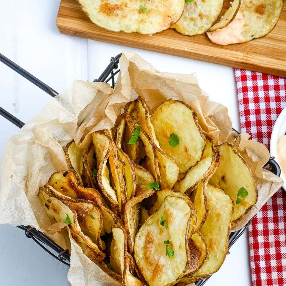 top view of air fried potato chips in a basket on a white board