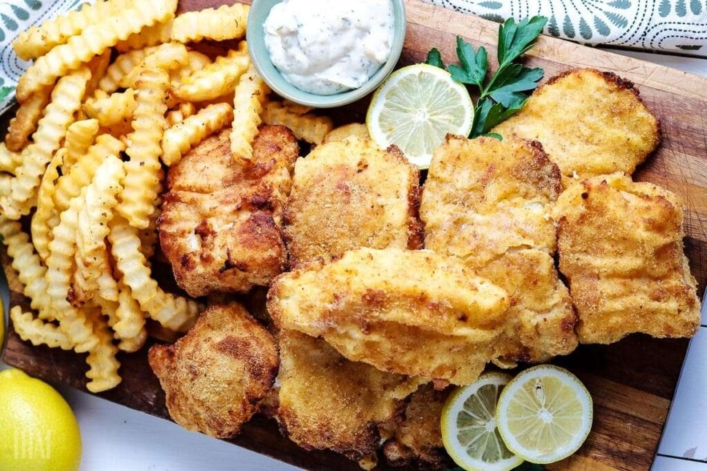 top view of crispy air fried cod next to french fries, lemon wedges, and tartar sauce