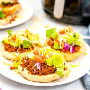 three air fryer navajo tacos with toppings on a white plate