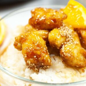 A picture of orange chicken on a bed of rice