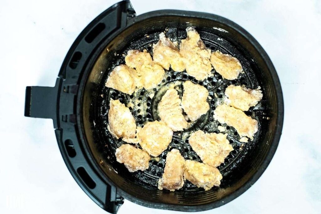 The battered chicken placed inside an air fryer before cooking