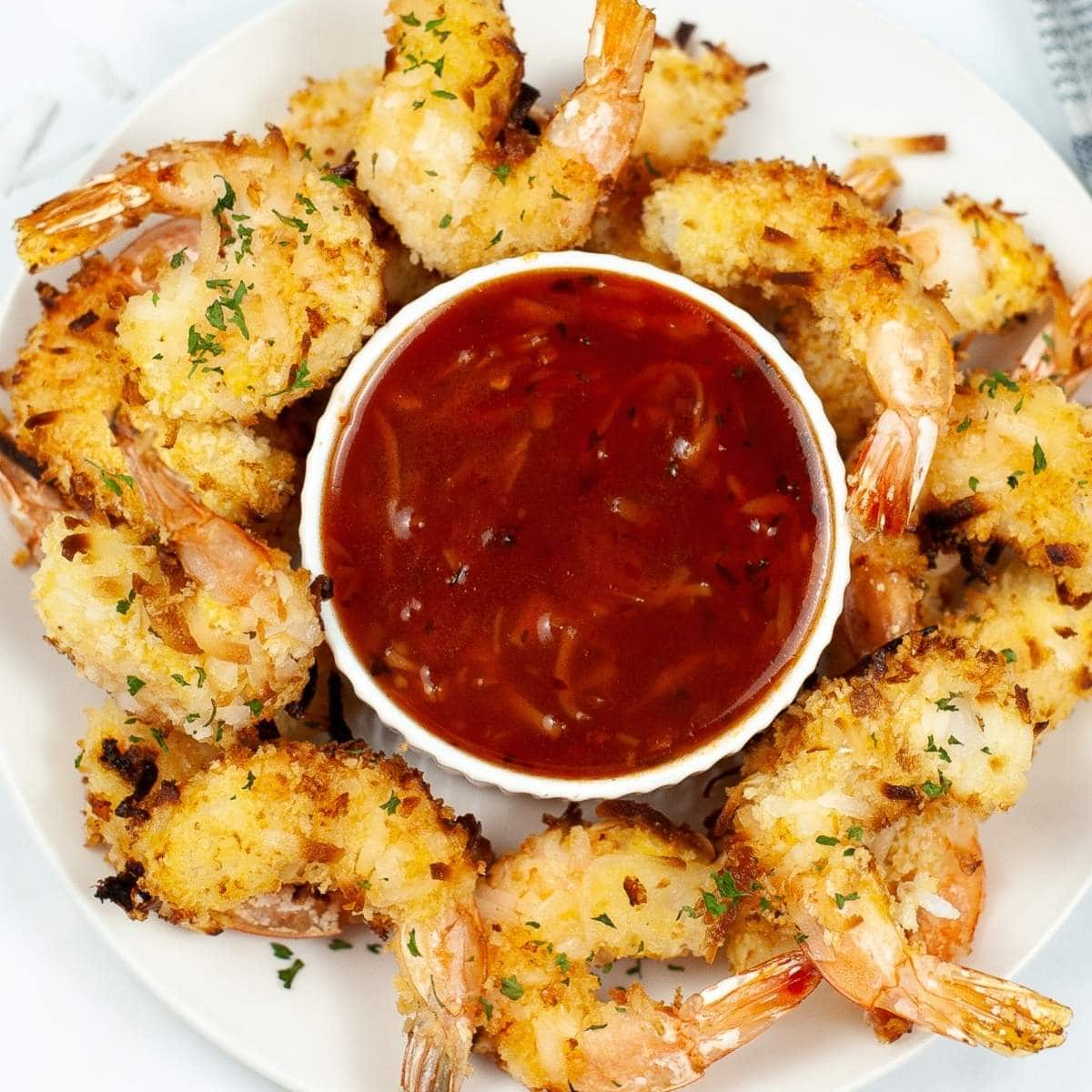 air fried coconut shrimp arranged around a cup of sauce on a white plate