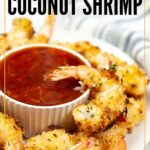 crispy air fryer coconut shrimp with a ramekin of red sauce in the middle with text overlay