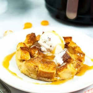 air fried bread pudding on a white plate topped with sauce and ice cream