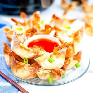 crab rangoon on glass plate with sweet and sour sauce