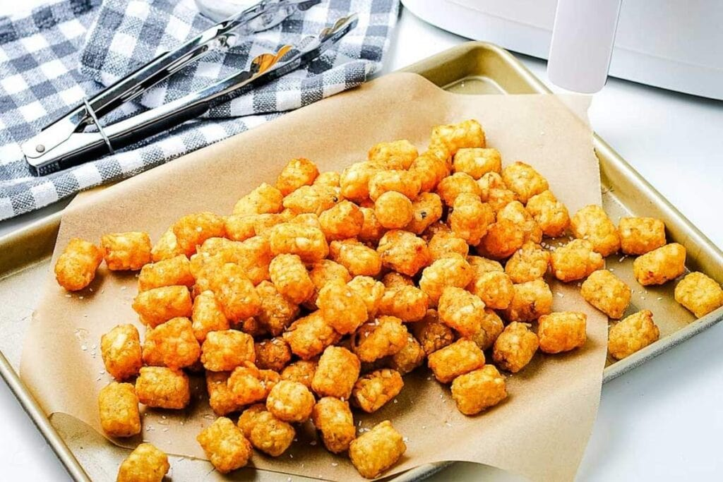 air fryer tater tots after cooking on baking sheet next to tongs