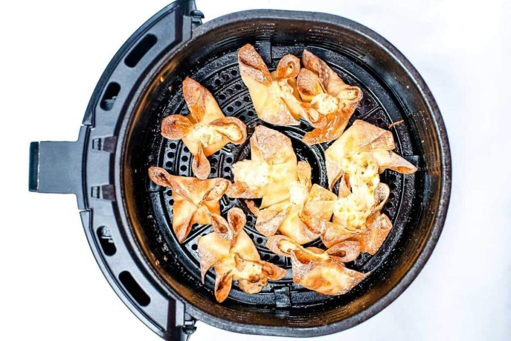 top shot of crab rangoons in the air fryer basket after cooking