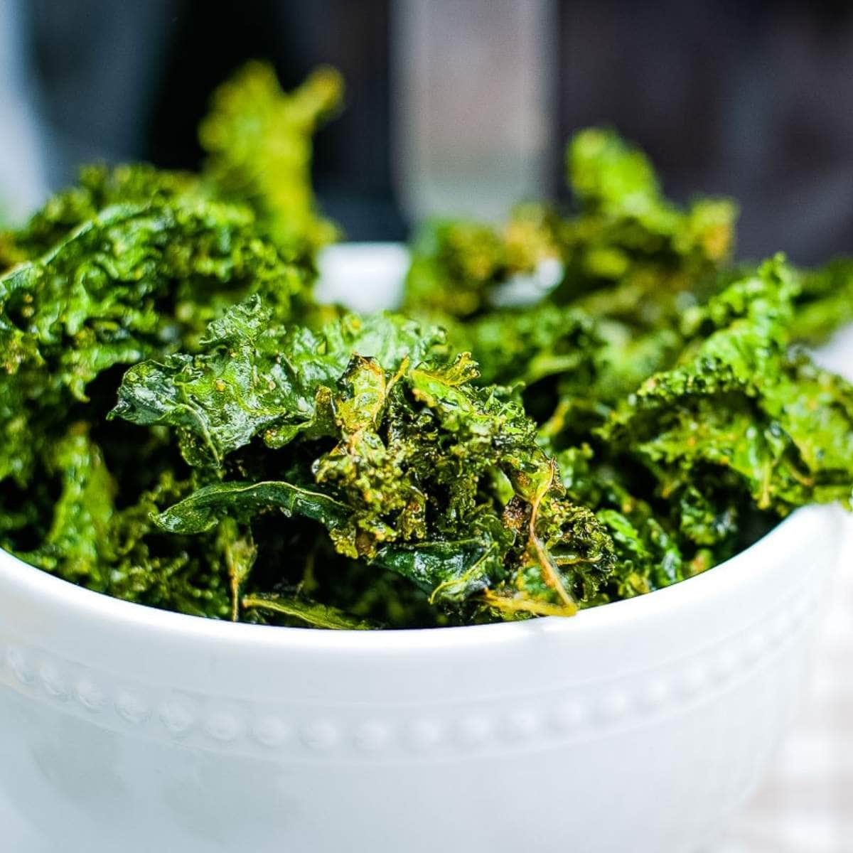 close up of air fried kale chips in a white bowl after cooking