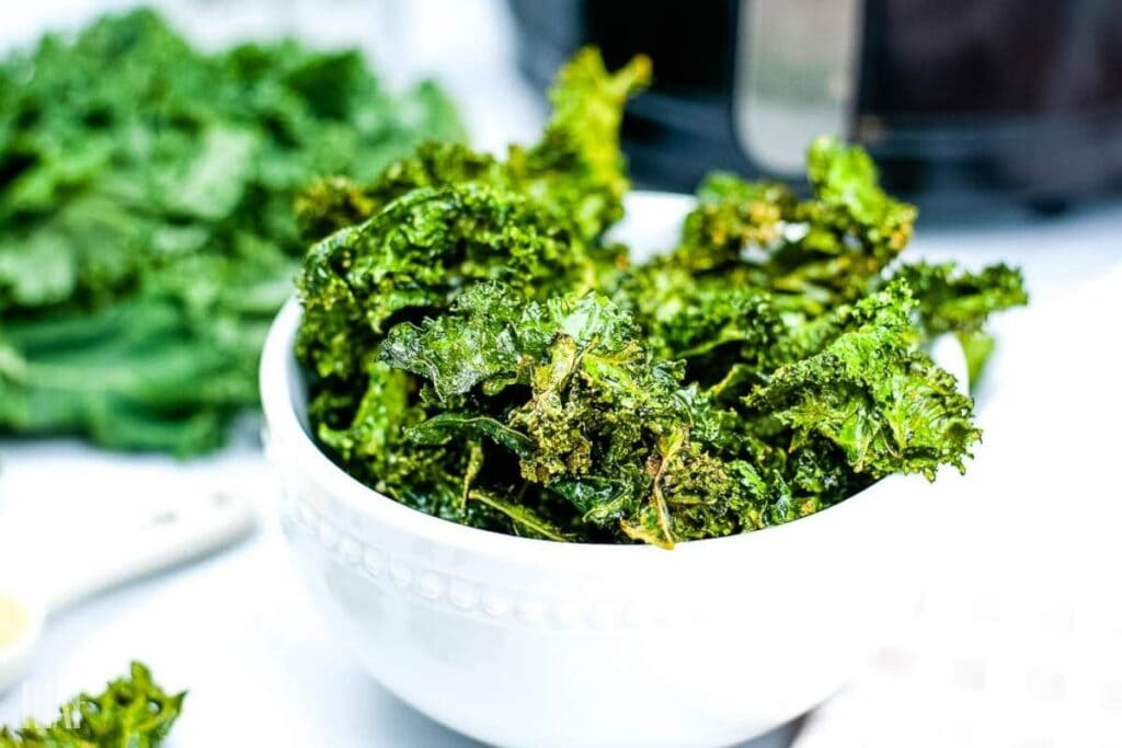 kale chips in a white bowl that was just cooked in the air fryer with more in the background